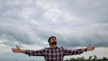 Mann steht entspannt und hebt die Hände in der Luft im Park