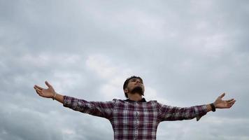 L'homme se tient détendu et lève les mains en l'air dans le parc video