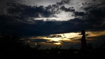 Silueta de una niña feliz caminando con la puesta de sol de fondo