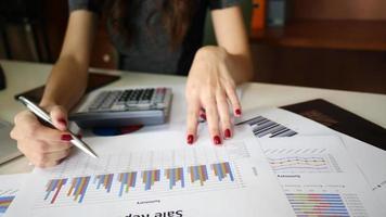 una mujer que usa sus manos para la contabilidad en una oficina usando una computadora portátil y una calculadora