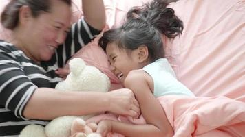 Funny mom and lovely child are playing in bedroom.