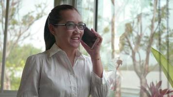 mulher asiática com as mãos usando telefone móvel inteligente na janela do escritório.