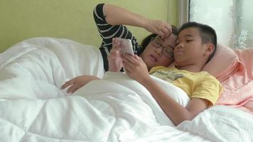 Happy mother and son hold tablet or smartphone lying on bed in bedroom. video