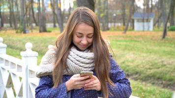 Mujer caucásica con bufanda tejida con teléfono inteligente, escribiendo algo durante la caminata en el parque de otoño