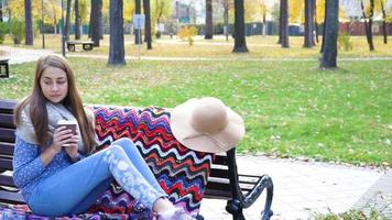 Woman Relaxes on the Bench in Beautiful Green Park with cup of coffee