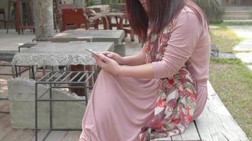 mulher asiática usando mídias sociais no parque. video