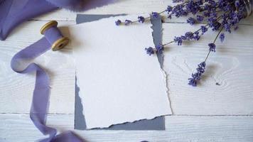 cartão em branco branco, envelope e fita em um fundo de tecido rosa e azul com flores de lavanda em um fundo branco. video
