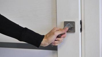 mão feminina abrindo e fechando uma porta de madeira branca