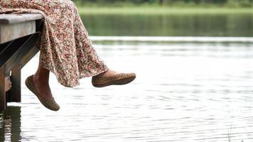Mujer balanceando su pie por el lago sentado en el borde de un muelle de madera