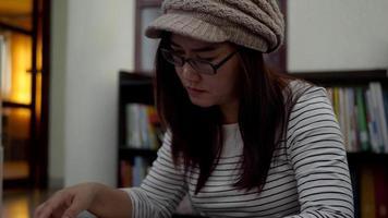 mulher está lendo um livro sentado no chão na biblioteca da universidade. video