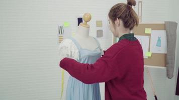 estilista asiático medindo um vestido em um manequim no estúdio.