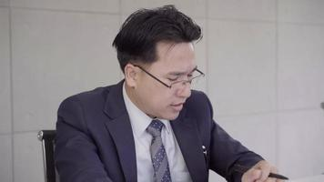 empresário asiático chateado na mesa do escritório