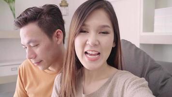 casal asiático usando videochamada de smartphone com um amigo na sala de estar em casa.