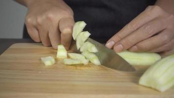 Chef mujer picar pepino en una tabla para cortar video