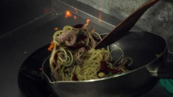 Slow motion - Chefs is preparing and cooking spaghetti food at the kitchen of a restaurant.