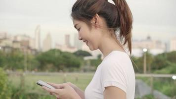 alegre mujer blogger turística asiática que usa tecnología de pantalla táctil en el teléfono inteligente mientras camina por la calle.