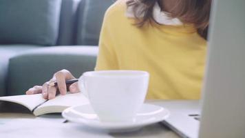 Asia empresaria escribiendo en un cuaderno video