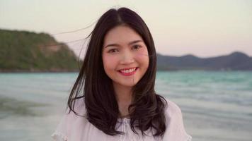 junge asiatische Frau, die sich am Strand glücklich fühlt.