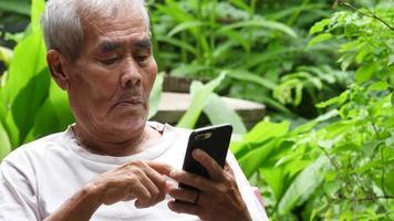 homem idoso deslizando em seu smartphone