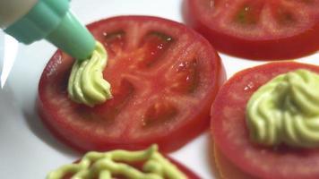 exprimir salsa sobre tomates picados