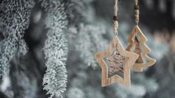 brinquedos de natal de madeira pendurados nos galhos de uma árvore de natal