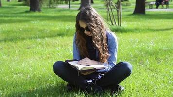 giovane donna che legge nel parco video