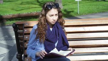 giovane donna legge seduto nel parco