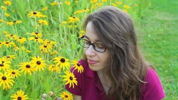 jovem sentindo o cheiro de flores amarelas video