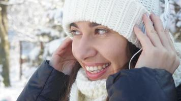 vrouw luisteren naar muziek in de sneeuw