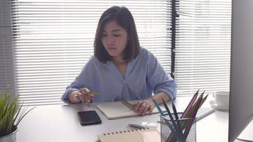 Asian woman in smart casual wear coming on computer while sitting on table in creative office. video