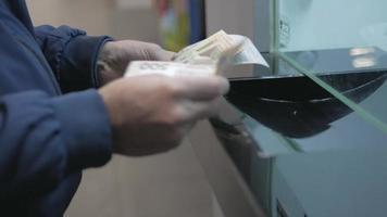 hombre cuenta dinero en la ventana del banco
