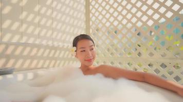jovem mulher asiática relaxando na banheira video