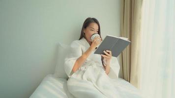 joven, mujer asiática, leer un libro, en cama