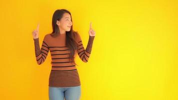 mujer señala con el dedo en el espacio en blanco con fondo amarillo