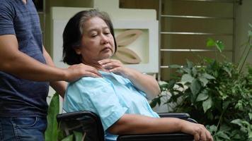 Mujer mayor discapacitada sentada en una silla de ruedas en un parque del hospital video