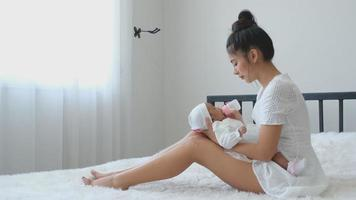 Young Asian Mother Gives a Bottle with Milk to Newborn Baby on Bed