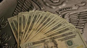 rotierende Stock Footage Aufnahme der amerikanischen Papierwährung auf einem amerikanischen Adlerschild Hintergrund - Geld 0401