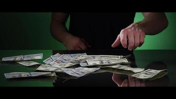 Hands of a man picking up $100 Bills off of a Reflective Surface - MONEY 0037 video