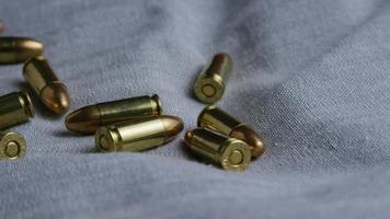Disparo giratorio cinematográfico de balas sobre una superficie de tela - balas 084