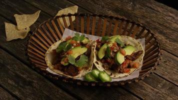 Foto giratoria de deliciosos tacos sobre una superficie de madera - BBQ 135