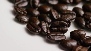 colpo rotante di deliziosi chicchi di caffè tostati su una superficie bianca - chicchi di caffè 044