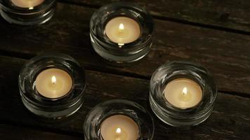 Velas de té con mechas en llamas sobre un fondo de madera - velas 001