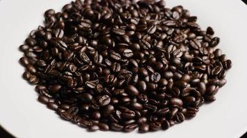 rotierender Schuss von köstlichen, gerösteten Kaffeebohnen auf einer weißen Oberfläche - Kaffeebohnen 064