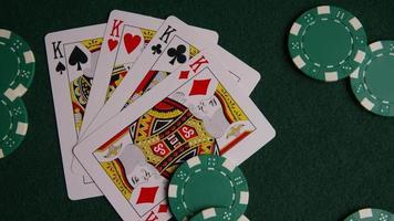 tiro giratório de cartas de pôquer e fichas de pôquer em uma superfície de feltro verde - pôquer 010 video