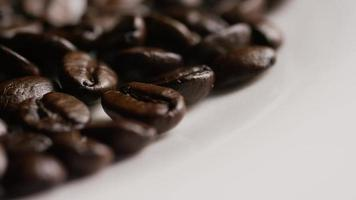 colpo rotante di deliziosi chicchi di caffè tostati su una superficie bianca - chicchi di caffè 052