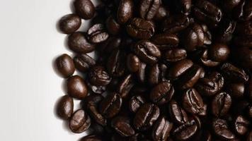 colpo rotante di deliziosi chicchi di caffè tostati su una superficie bianca - chicchi di caffè 062