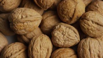 filmische, roterende opname van walnoten in hun schelp op een wit oppervlak - walnoten 052