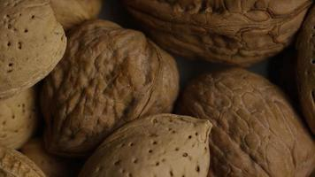 Cinematic, rotating shot of a variety of nuts on a white surface - NUTS MIXED 009