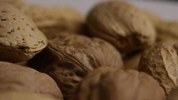 Cinematic, rotating shot of a variety of nuts on a white surface - NUTS MIXED 033