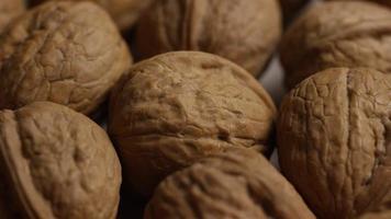 filmische, roterende opname van walnoten in hun schelp op een wit oppervlak - walnoten 016